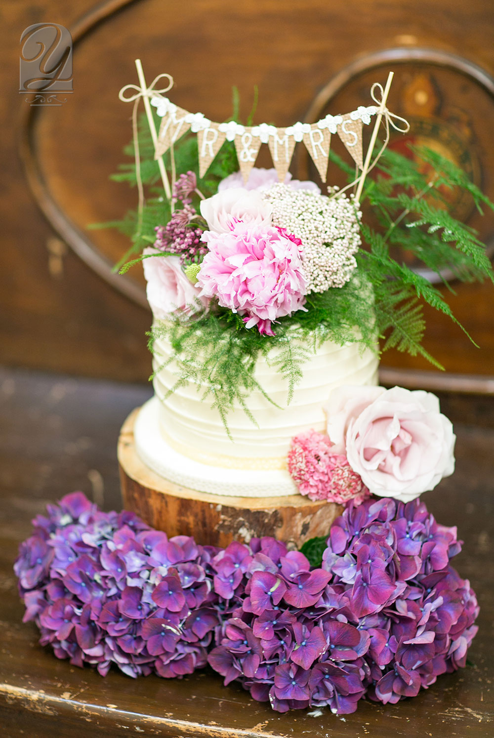 Created by Unique Cakes by Yevnig, this rustic buttercream finished round-tier cake is elegantly topped by a small fresh flower bouquet, co-ordinating with the brides' hand tie. Natural tree trunk slices present a complementary selection of delicious cupcakes