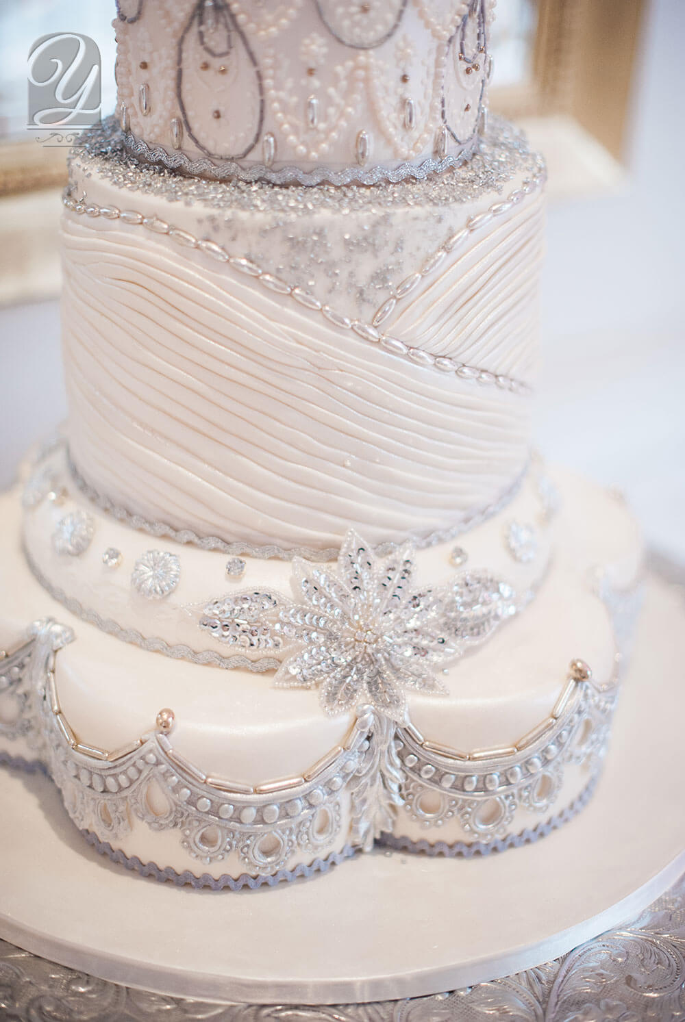 The Alexandria Chic a truly unique grand 5 tier centrepiece designer wedding cake from Unique Cakes, by Yevnig. A stunning combination of diamonds, silver jewellery and delicate lacework.