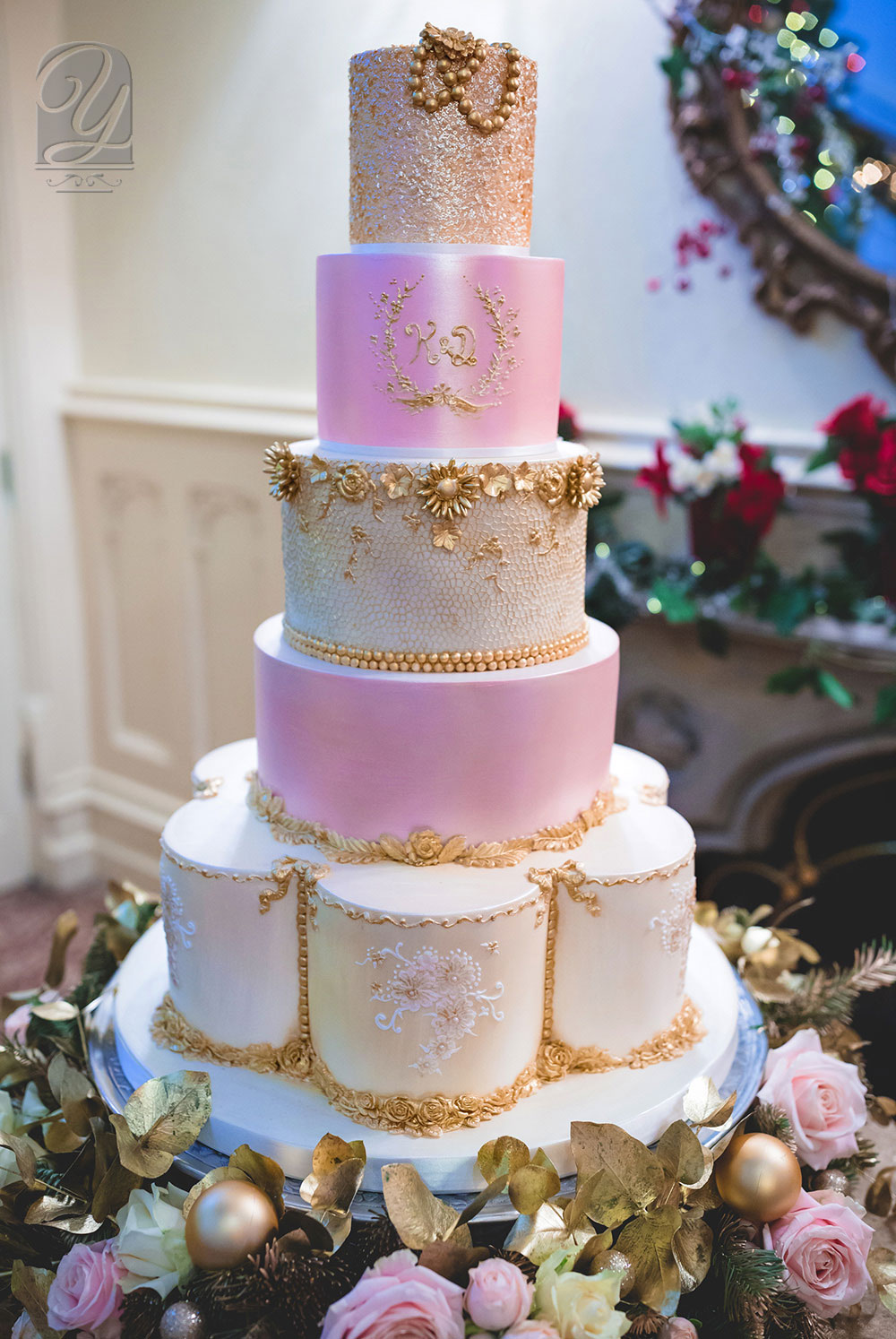Five tier golden luxury wedding cake with gilded crest of the couple's initials, broches and beading. Delicate lacework and hand-piped royal iced flowers with ornate rose-gold sequin top cake from Unique Cakes by Yevnig